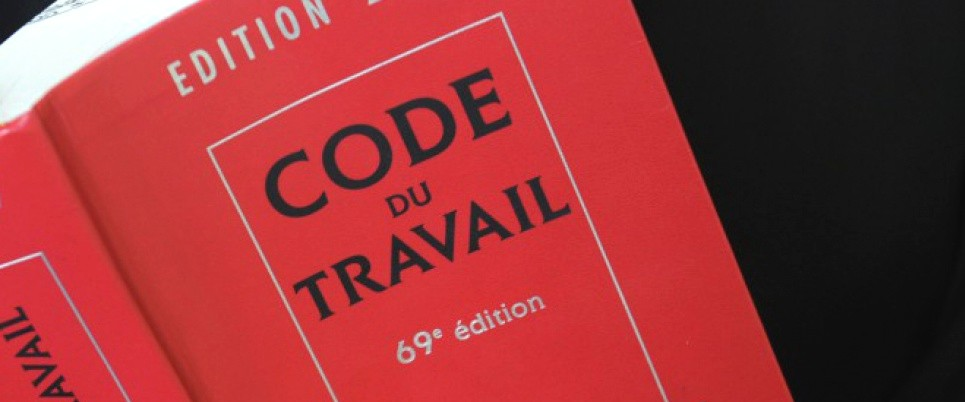 """A lawyer reads a copy of the French labour code (""""code du travail"""" in French), on May 24, 2012 in Quimper, western France. AFP PHOTO / FRED TANNEAU"""